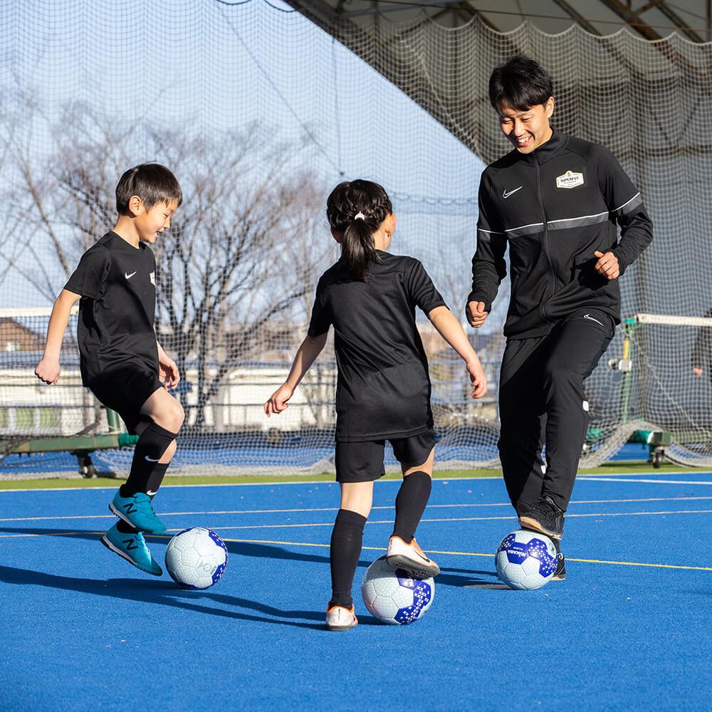 指導するコーチと男の子・女の子