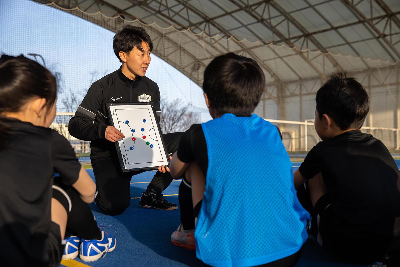 ホワイトボードを使って戦術指導でするコーチと子どもたち