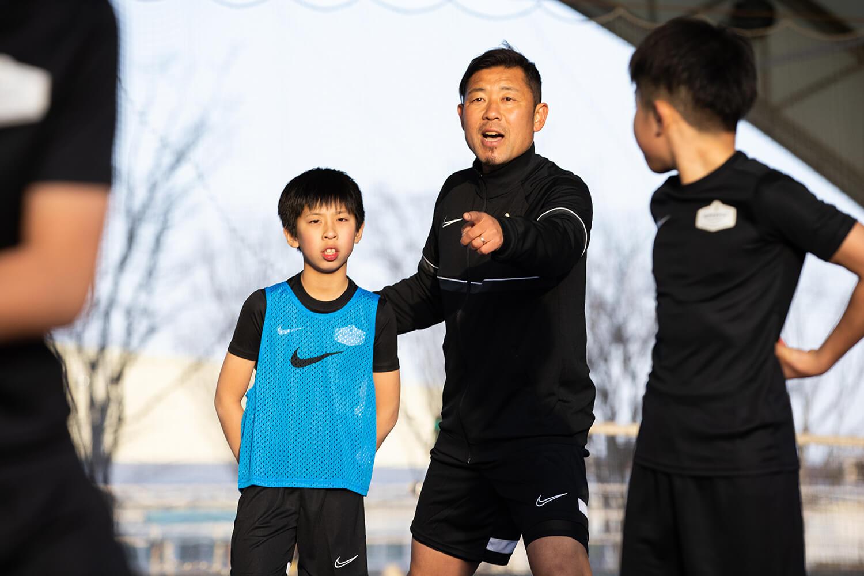指さして指導するコーチと子どもたち