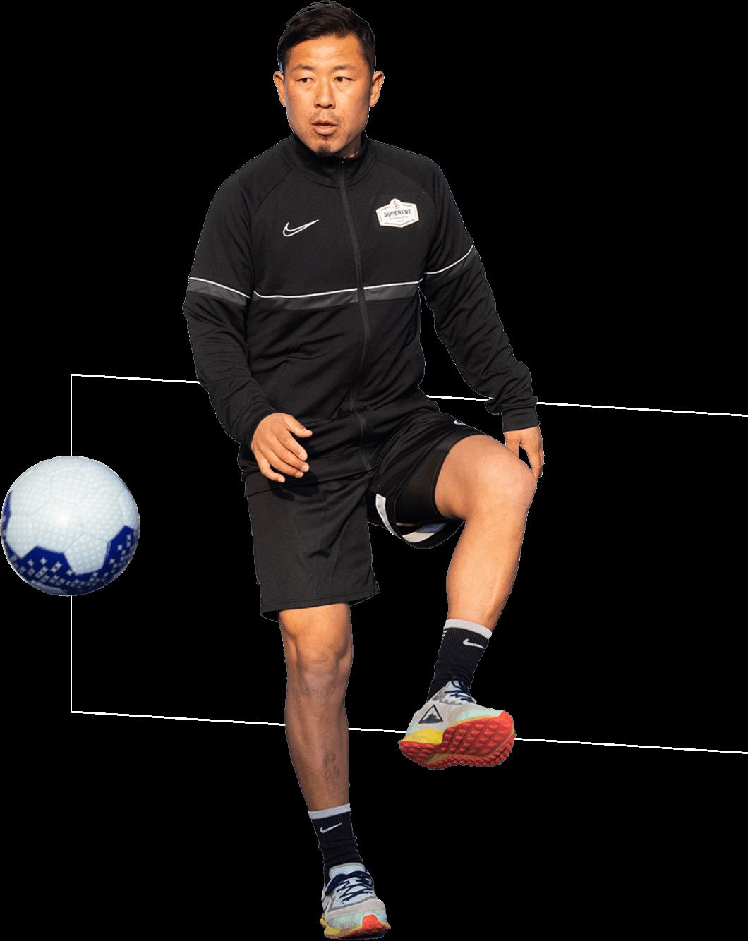 ボールを蹴るコーチ