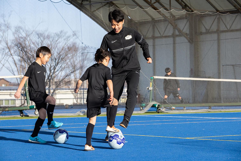 フットサルの練習にはげむ少年少女とコーチ