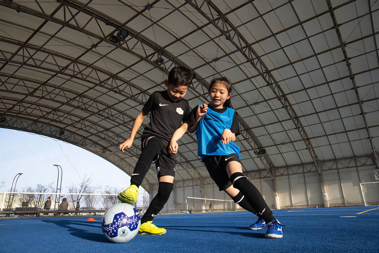 フットサル場でボールを取り合う少年と少女